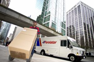 Hand delivery of packages by a Purolator employee in a city