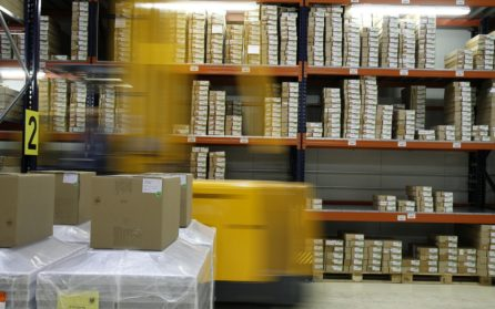 Forklift moving in a warehouse with large shelves of packages