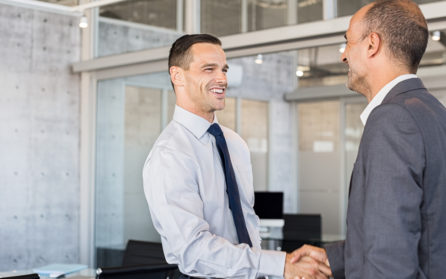 Two smiling businessmen shaking hands while standing in modern office boardroom. Happy business men shaking hands and looking at each other.