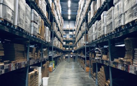 Warehouse aisle with towering shelves full of packages