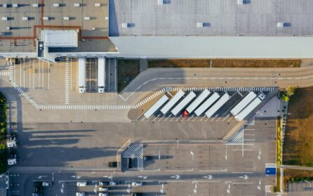 Overhead view of shipping warehouse with trucks in parking lot